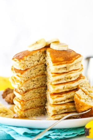 A stack of banana pancakes with one piece missing and slices of bananas on top