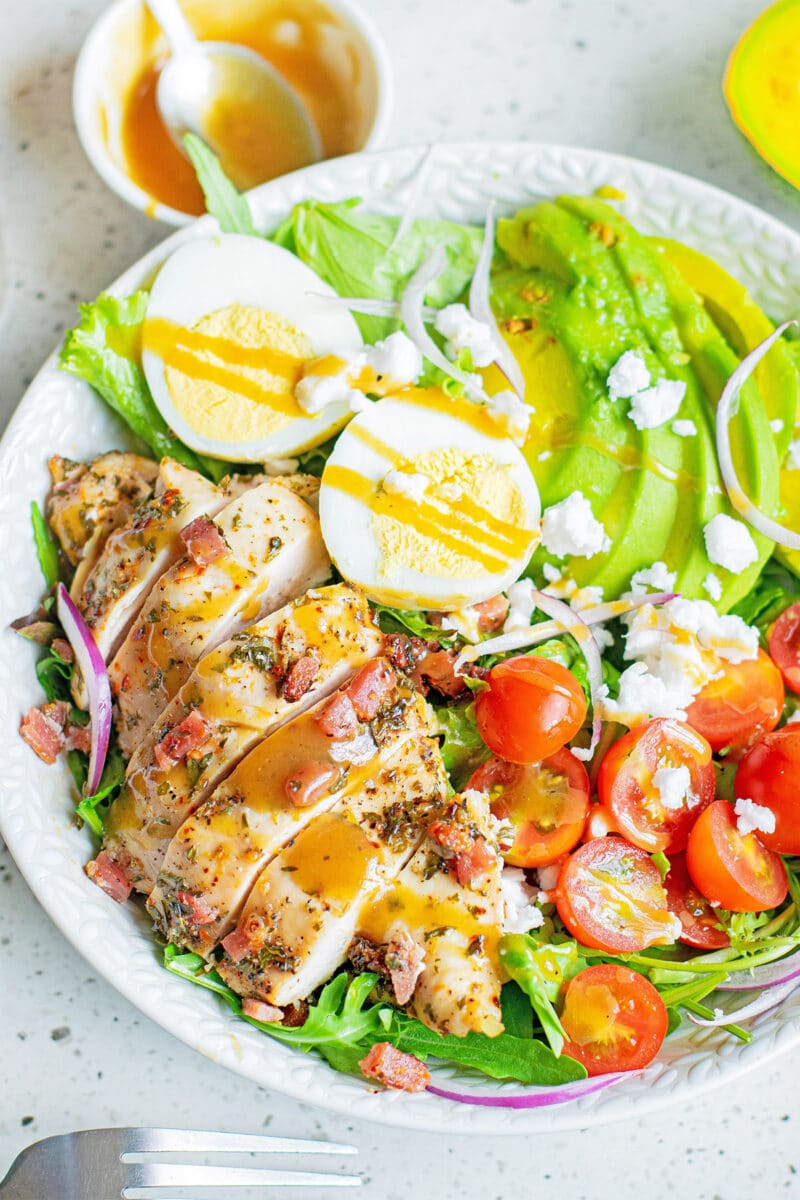 herb chicken cobb salad with dressing in white bowl