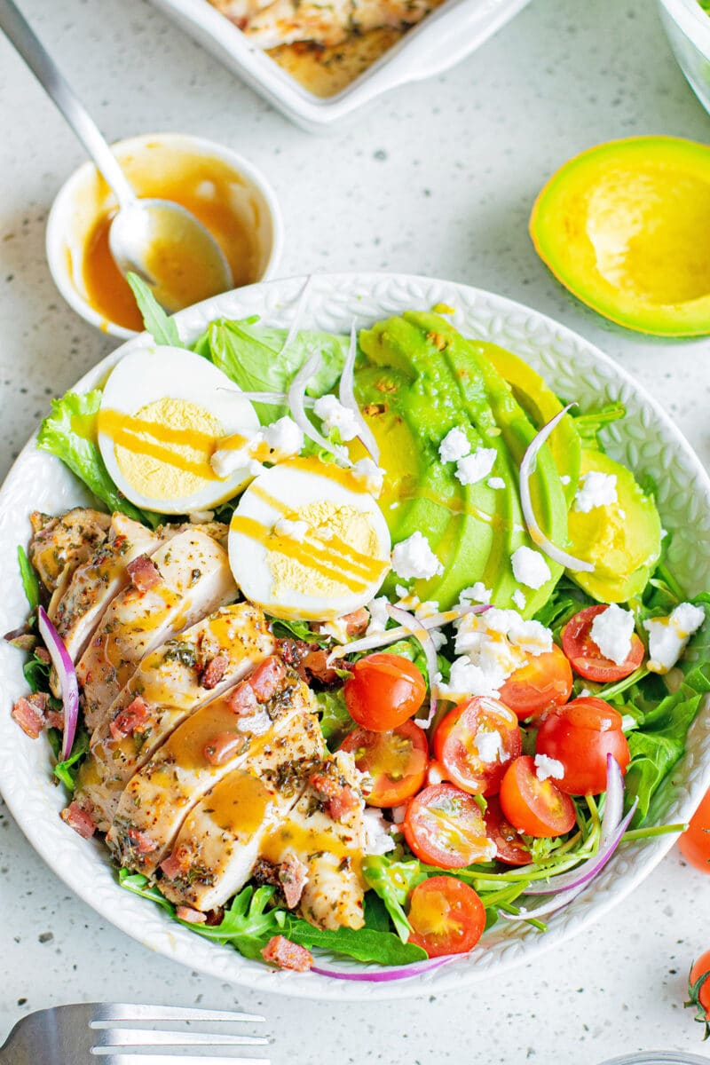 herb chicken cobb salad with dressing in white bowl with dishes around it