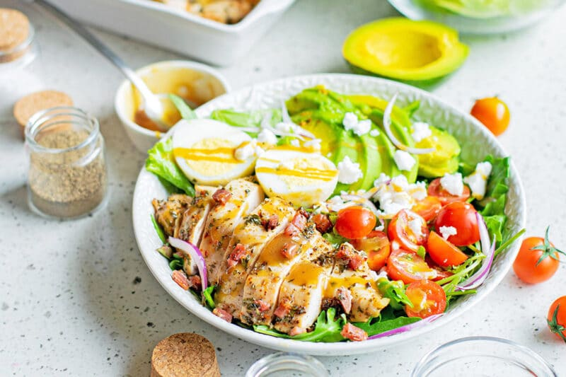 cobb salad on white surface with dishes and ingredients around it