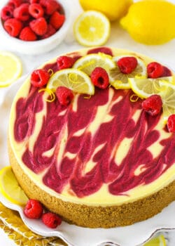 A slice of lemon raspberry swirl cheesecake topped with raspberries and lemon