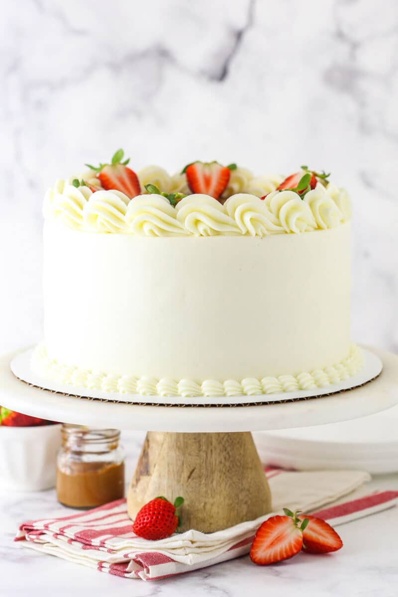 Strawberry Dulce De Leche Cake with white frosting on marble and wood cake stand