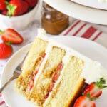 slice of Strawberry Dulce De Leche Cake with strawberries and dulce de leche in background