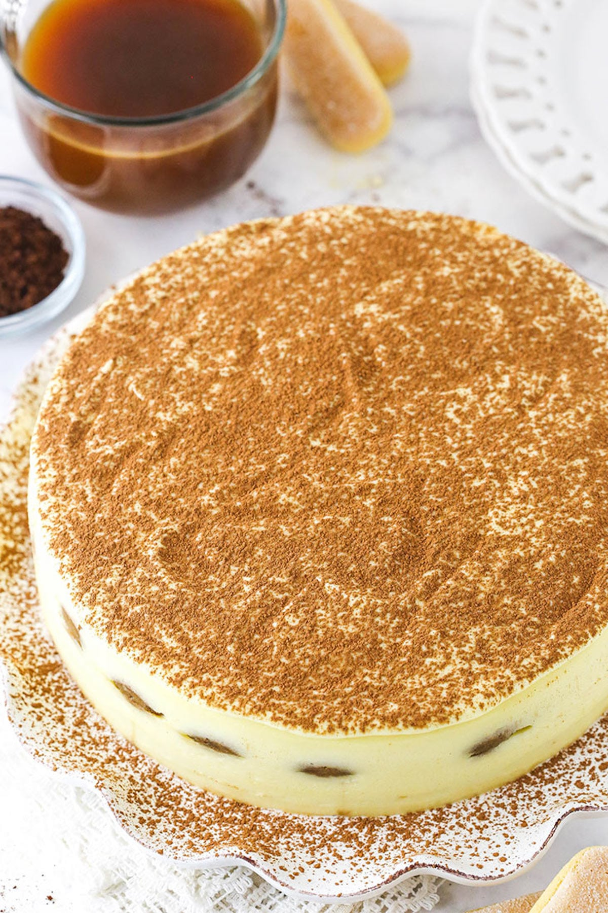 A Whole Tiramisu Cake on Top of a Cake Platter with a Sprinkling of Cocoa Powder on Top