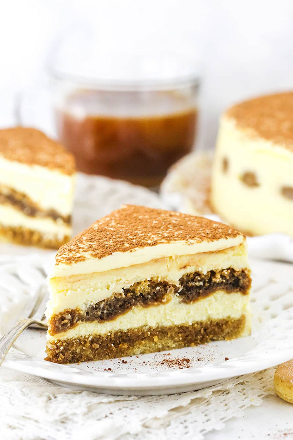 A Piece of Tiramisu Cheesecake on a Plate with a Second Slice and the Full Cake in the Background