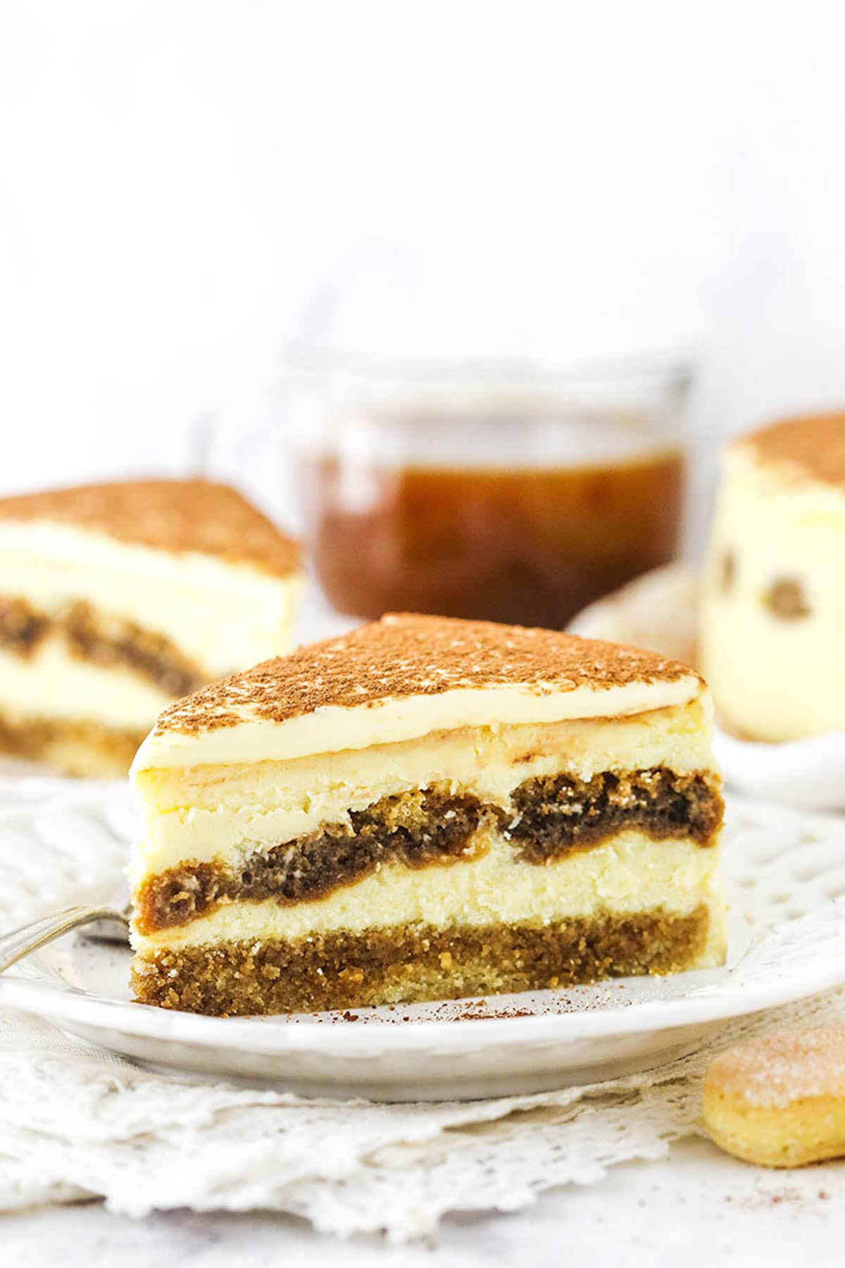 A Slice of Tiramisu Cake Sitting on a White Plate on Top of a Pile of Doileys