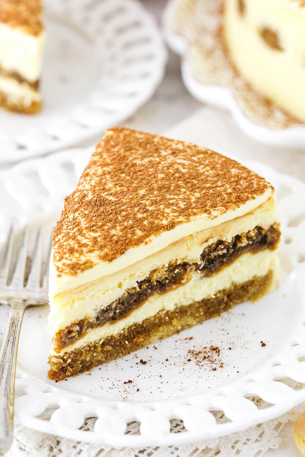 A Piece of the Ultimate Tiramisu Cheesecake on a White Plate with Decorative Edges