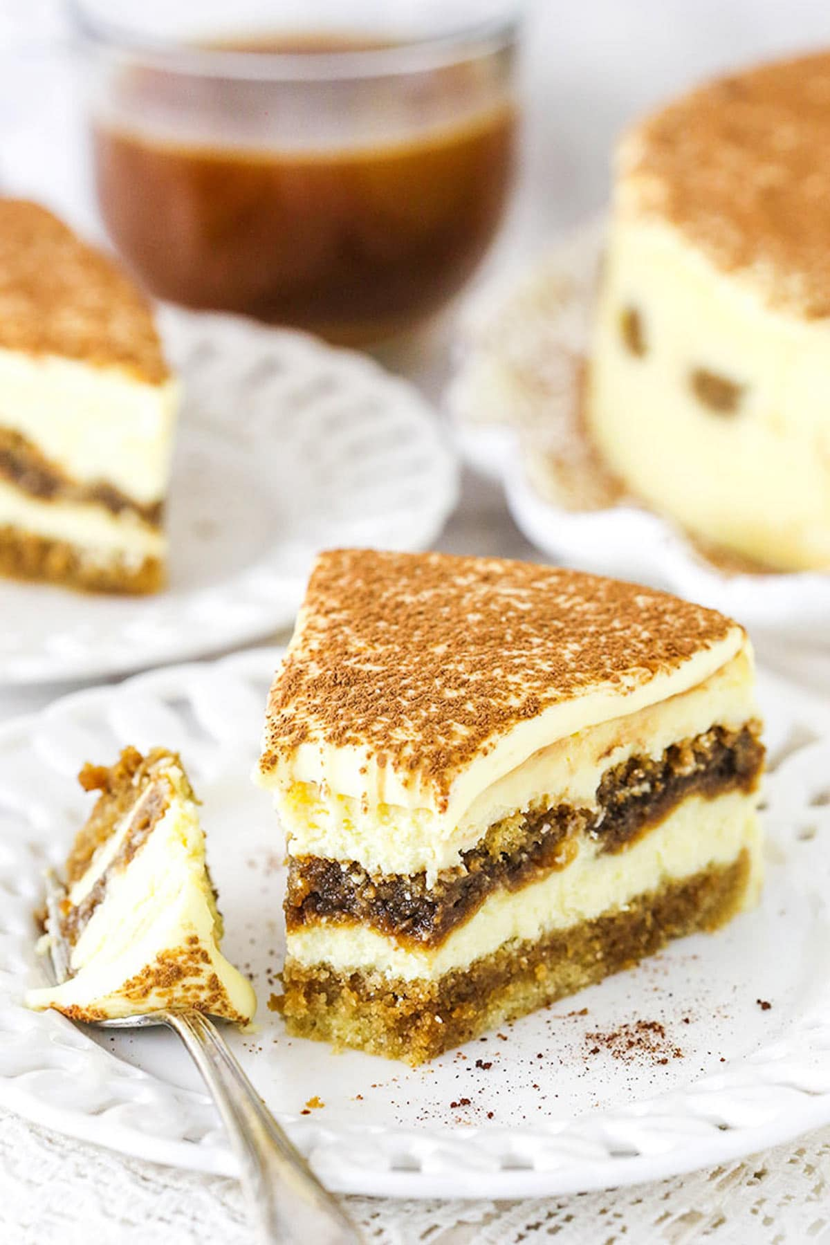 A Slice of Tiramisu Cheesecake on a Plate with One Bite on a Metal Fork
