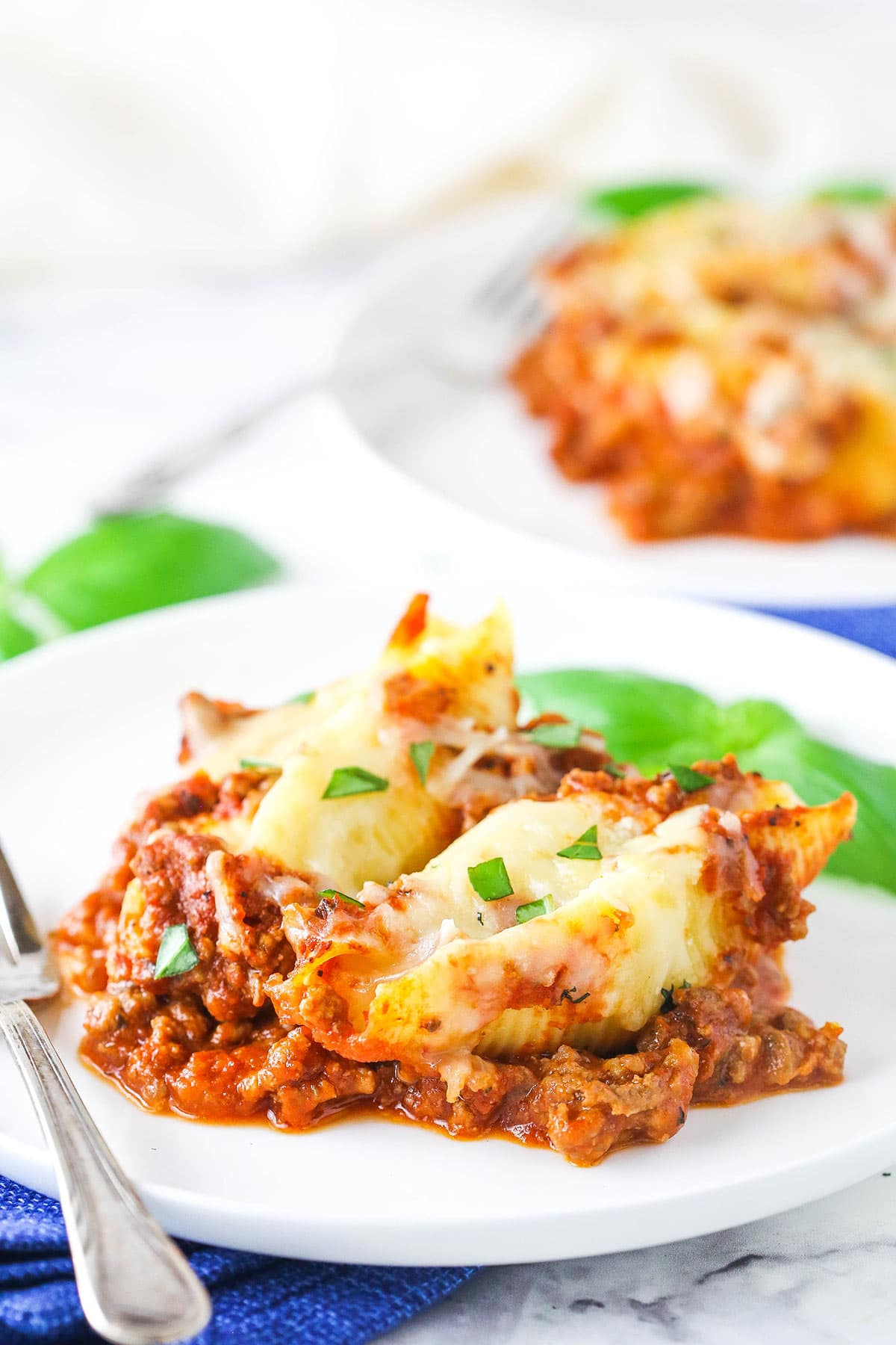 Ricotta stuffed shells with meat sauce on a white plate