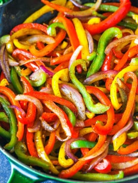 Sliced red yellow and green bell peppers and onions in a skillet
