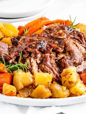 Shredded instant pot pork roast on a platter with potatoes and carrots