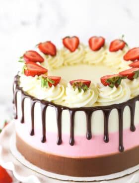 A neapolitan cake decorated with vanilla buttercream swirls, strawberry slices and drips of chocolate ganache