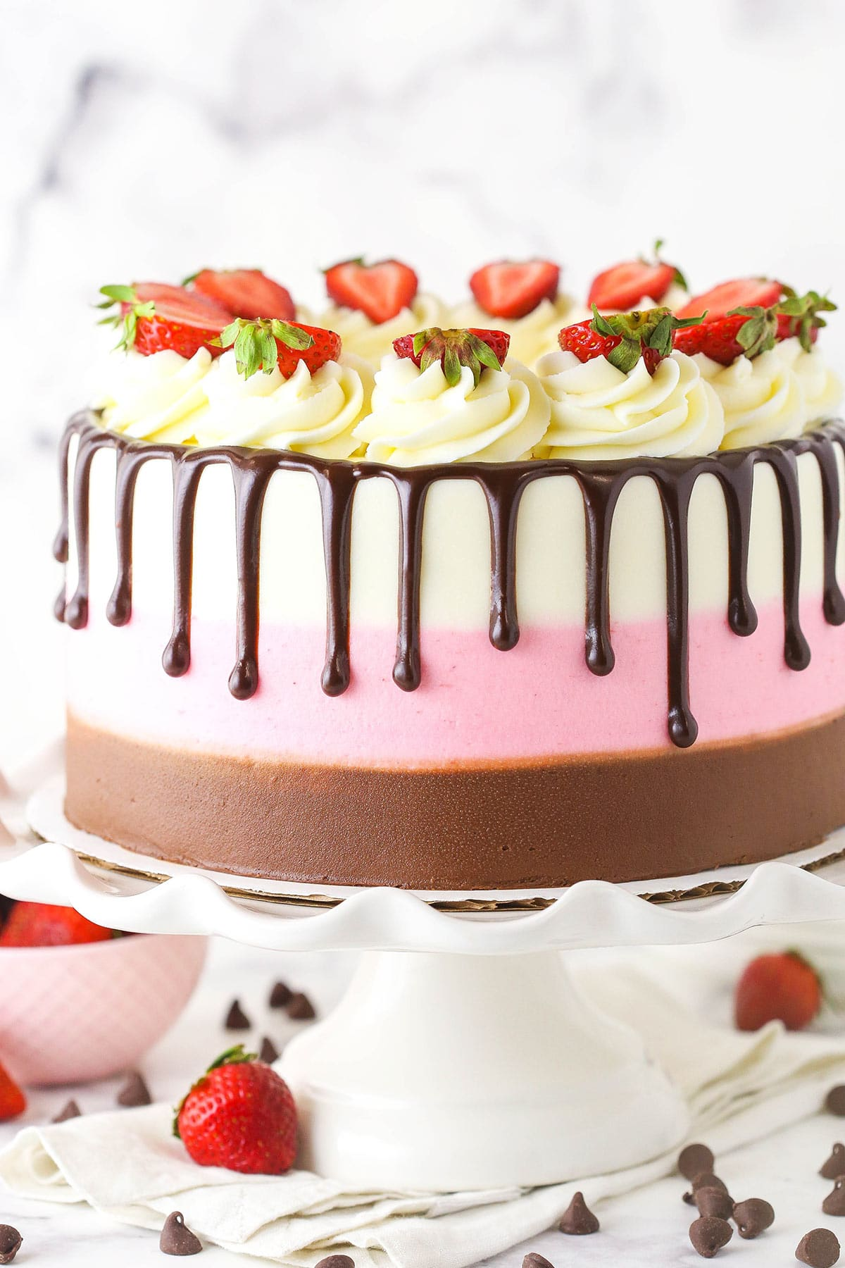 A close-up shot of a neapolitan cake with chocolate, vanilla and strawberry buttercream frosting