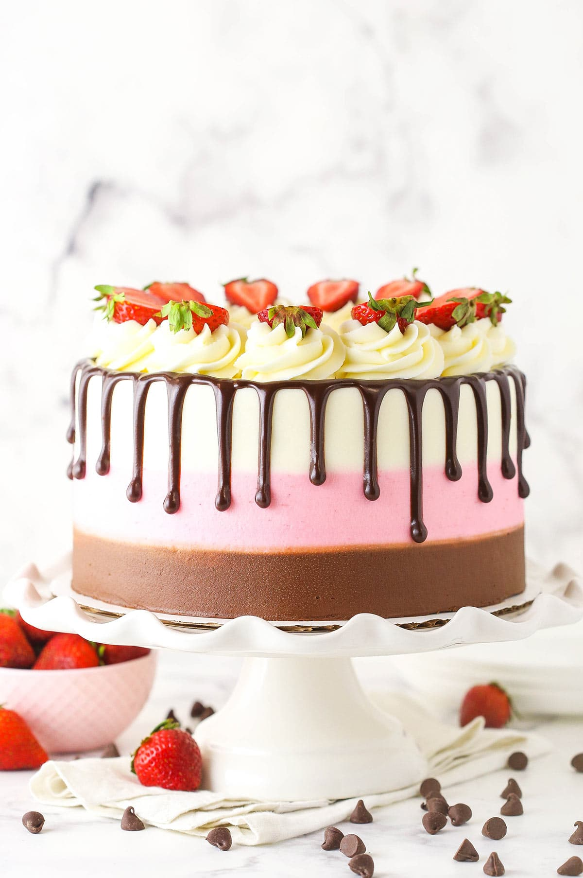 A neapolitan cake sitting on a white cake stand with strawberries and chocolate chips on the counter below
