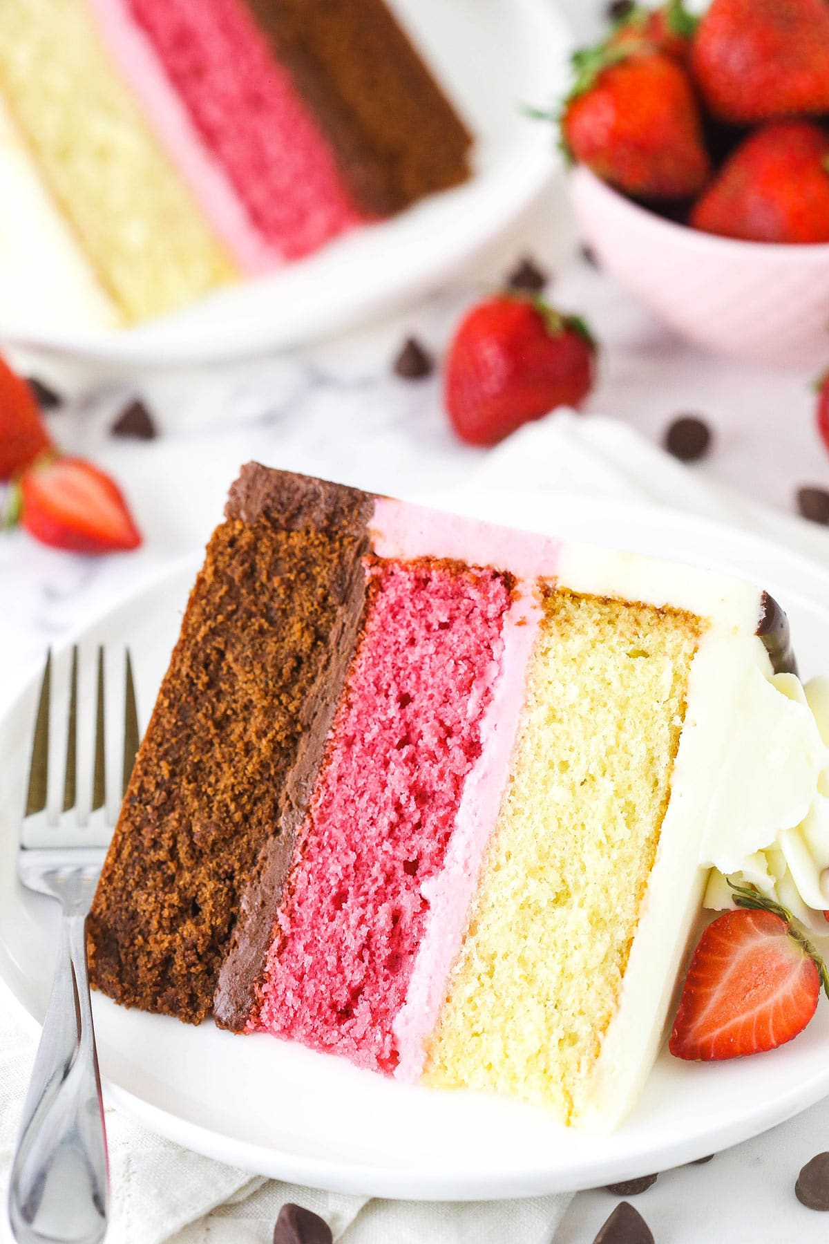 A large slice of neapolitan cake on a plate with a sliced strawberry