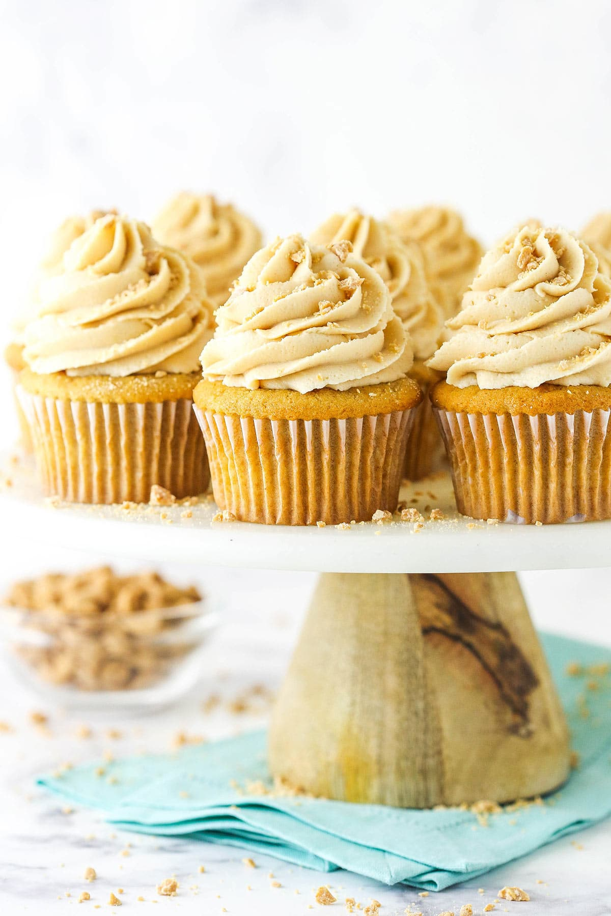 A close-up shot of homemade cupcakes on a white cake stand with a wooden base