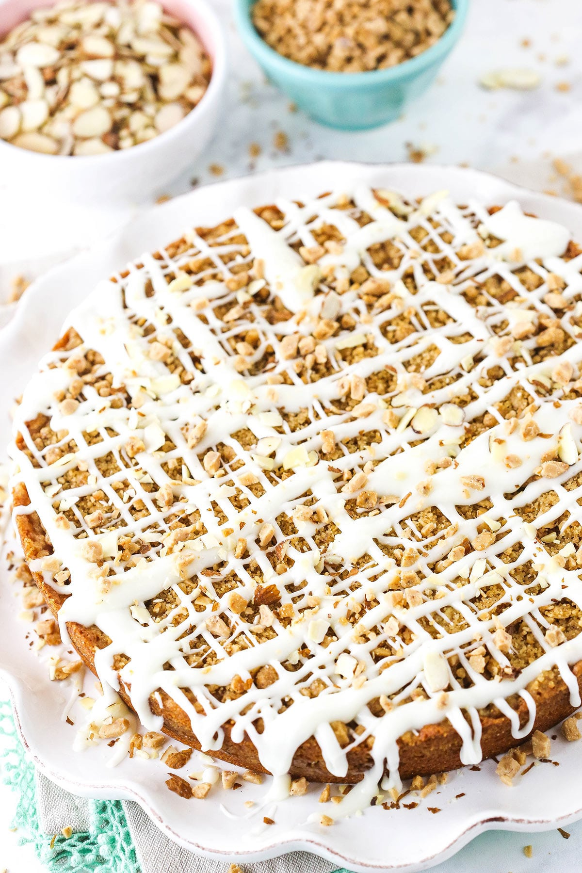 A coffee cake covered in drizzles of glaze, slivered almonds and toffee bits