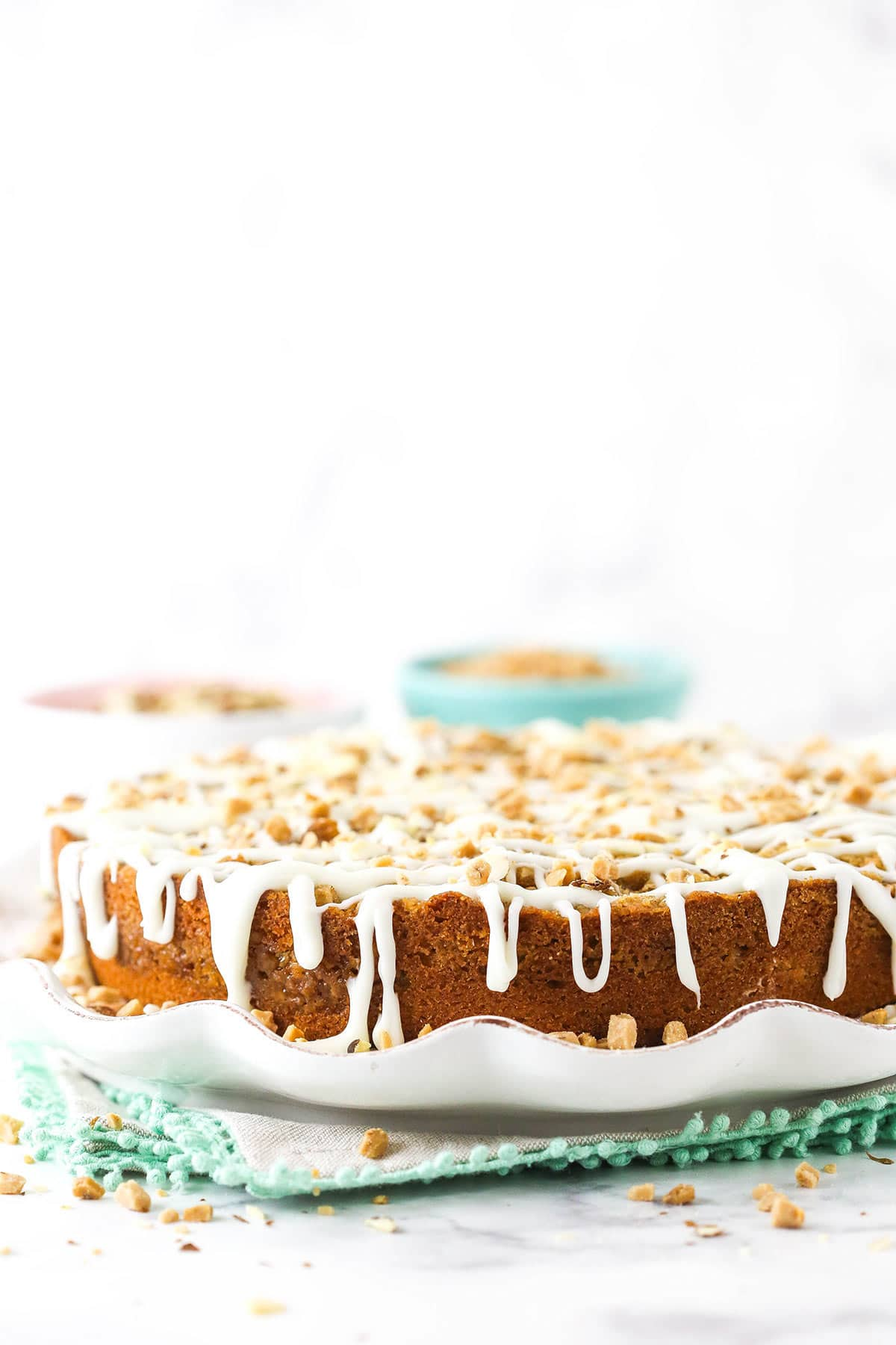A glazed breakfast layer cake on a cake stand over three stacked placemats