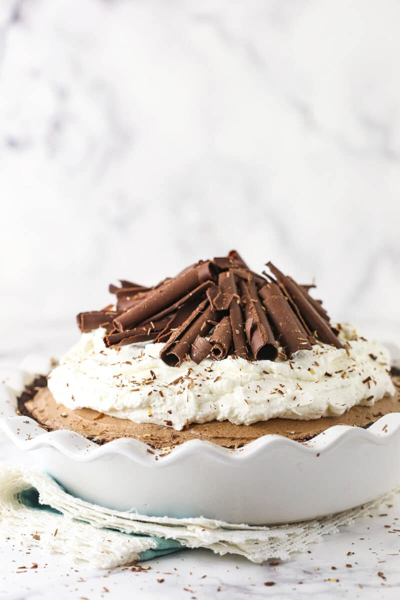 french silk pie in white pie dish with whipped cream and chocolate curls on top