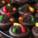 Chocolate cookies stuffed with buttercream frosting, covered with Oreo crumbs and topped with gummy worms