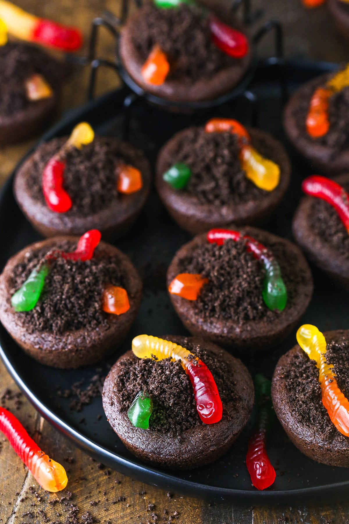 A round, black platter full of Halloween cookies topped with crushed Oreo cookies and two gummy worms