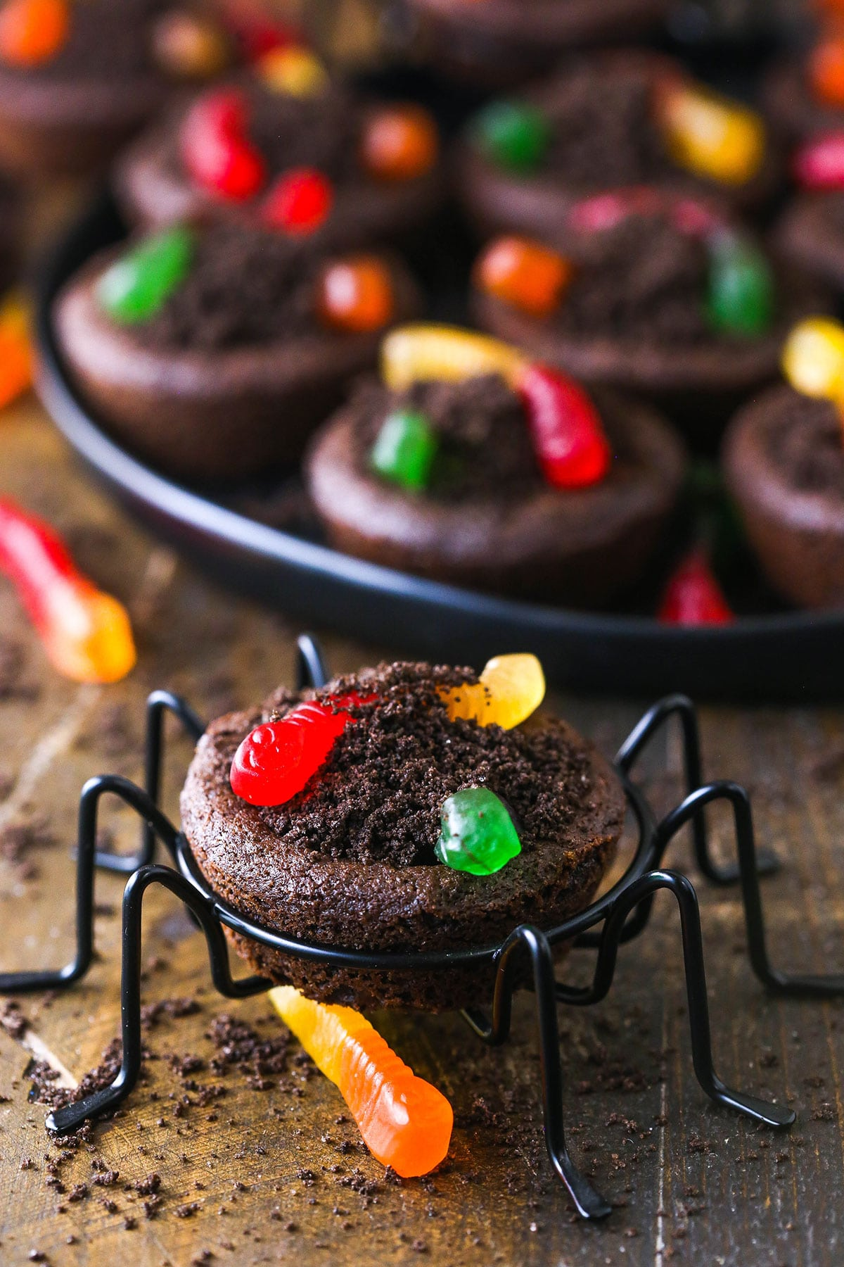 A dirt cookie cup on a small spider stand with a tray full of cookies in the background