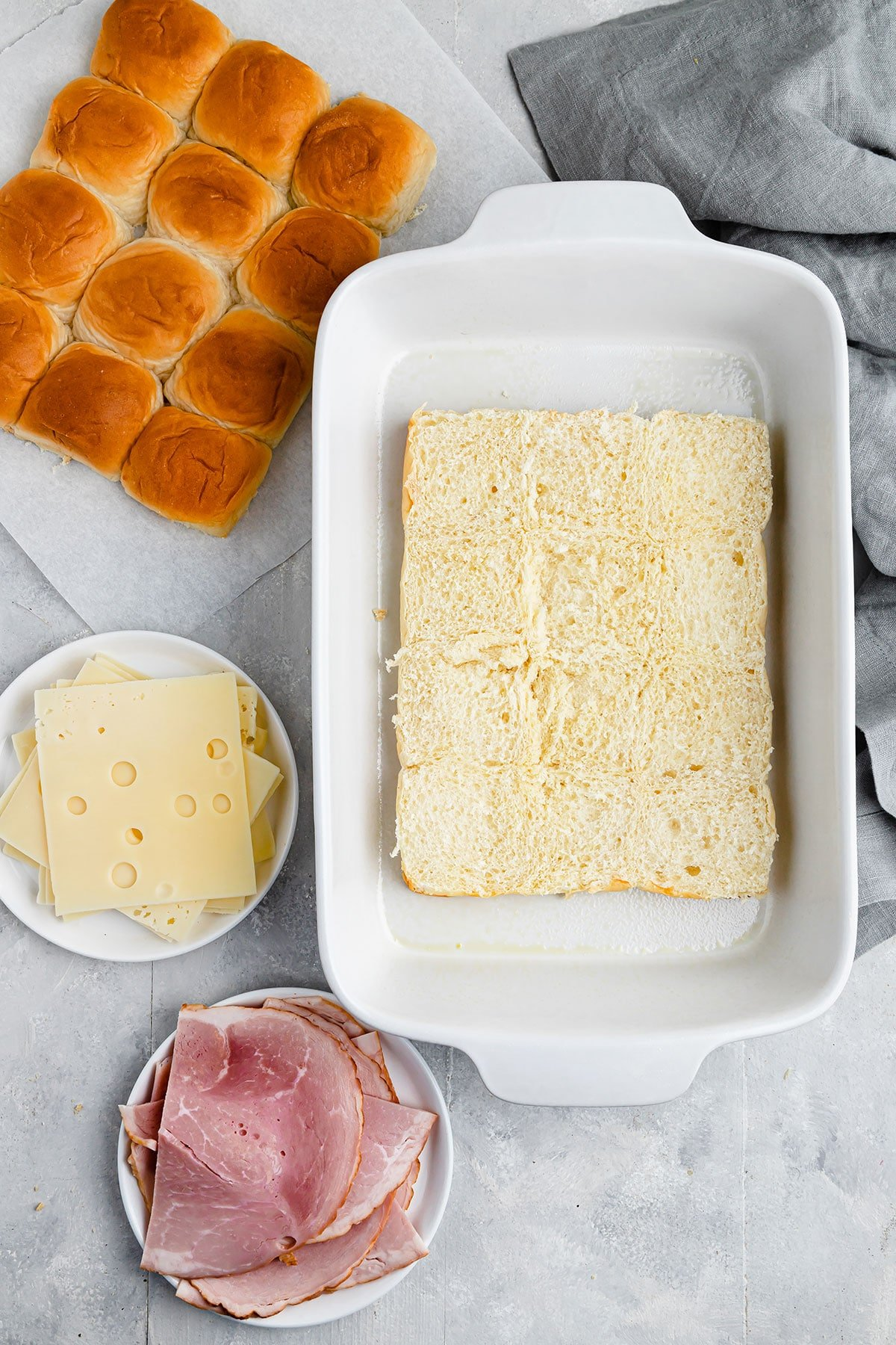 Halved Hawaiian rolls, Swiss cheese and ham on a gray countertop beside a kitchen towel