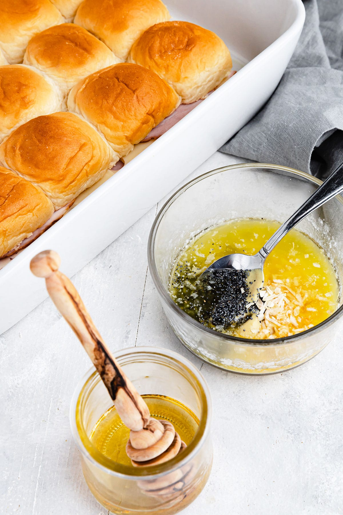 A bowl of honey beside a bowl containing the remaining glaze ingredients with the sliders in the background