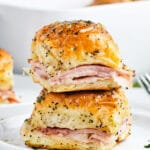 Two ham and cheese sliders stacked on top of one another on a plate