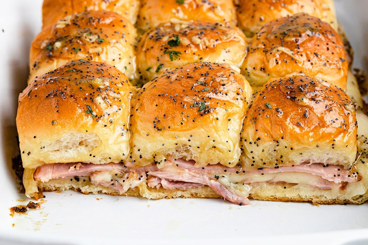A baking dish full of freshly baked ham and cheese sliders