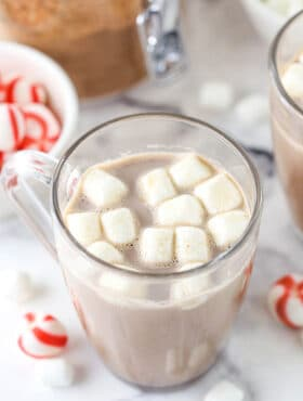 A serving of hot cocoa in a glass mug with melting mini marshmallows on top