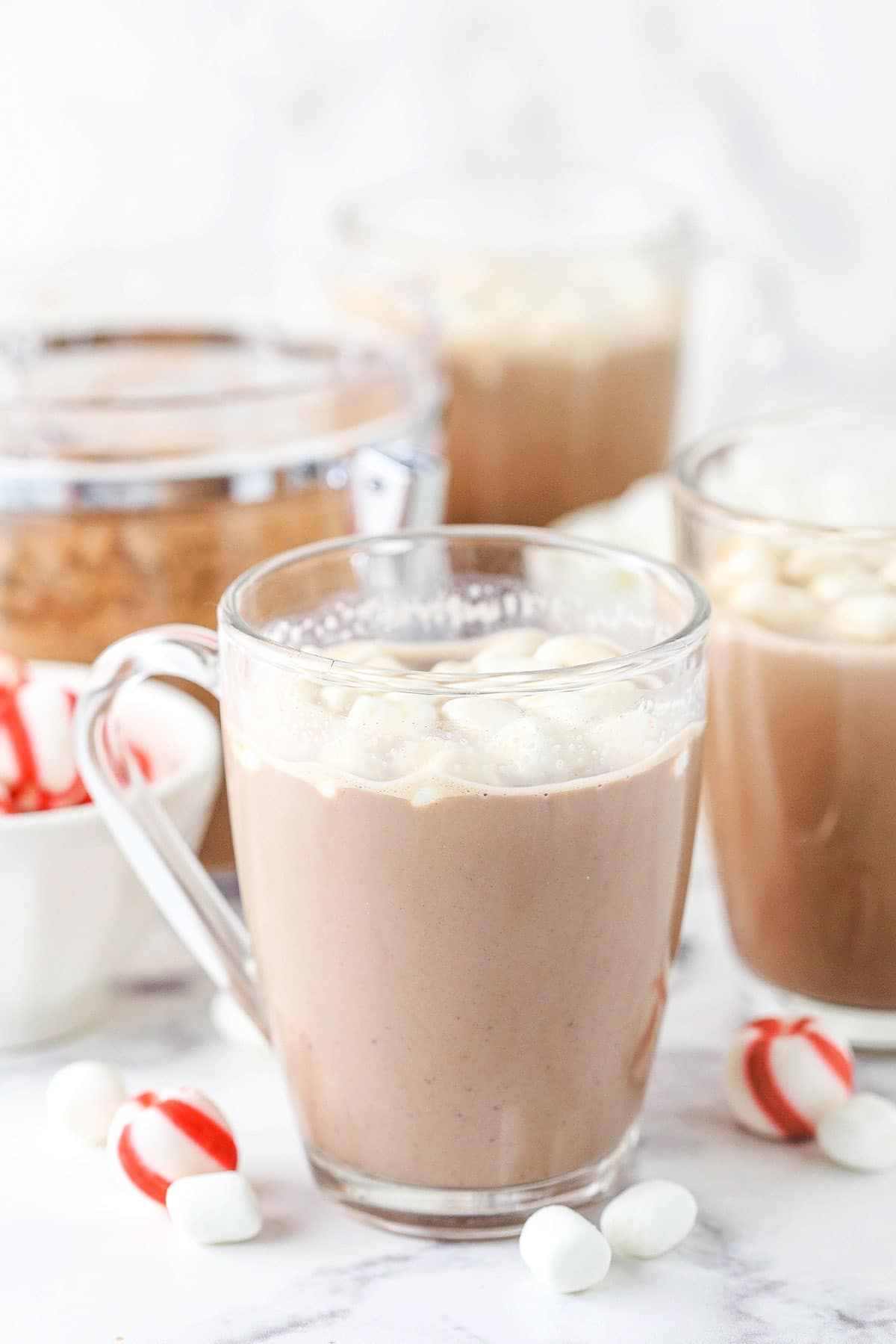 A glass mug full of homemade hot cocoa with peppermint candies in a bowl beside it