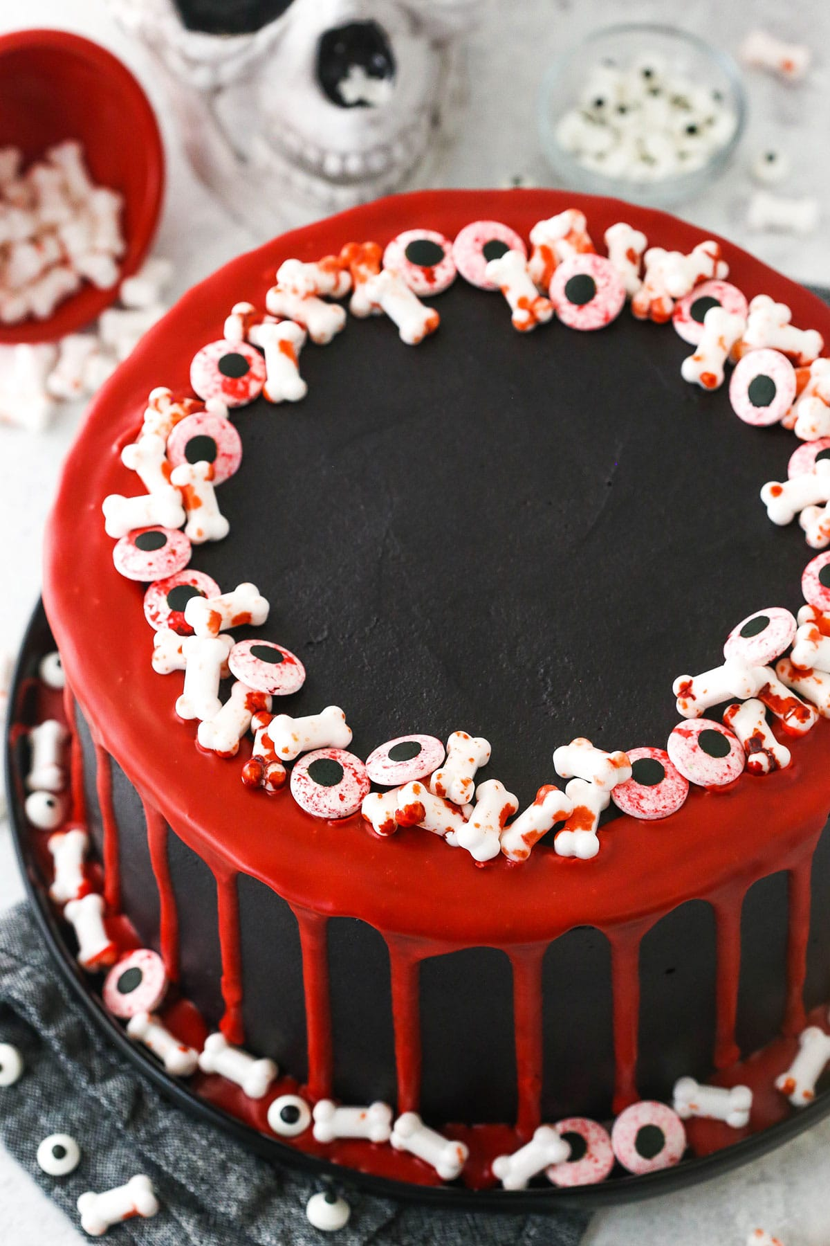 red and black halloween cake on black platter with skull in background
