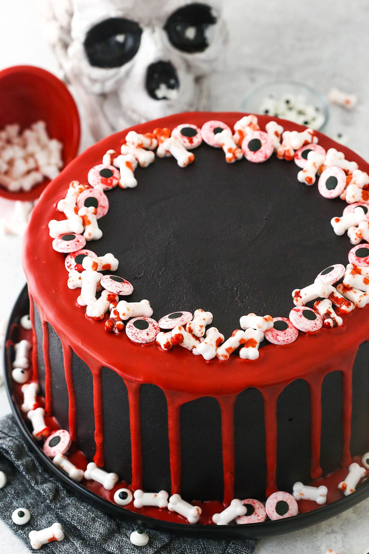 red and black cake with red drip and bone and eye sprinkles
